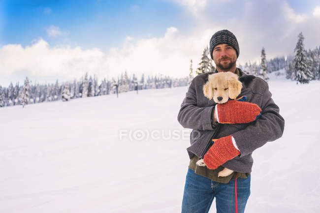 Man holding golden retriever puppy dog in coat in winter landscape — Stock Photo