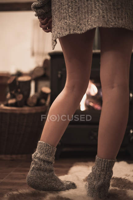 Cropped image of attractive woman with beautiful skin in sweater and socks standing on carpet in front of fireplace at home — Stock Photo