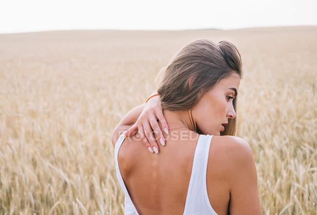 Задний вид женщины, стоящей на пшеничном поле и касающейся спины — стоковое фото