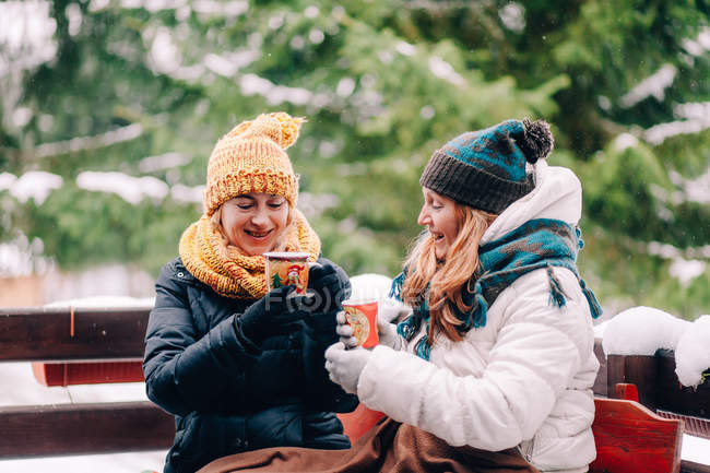 Two women sitting in snow with hot drink — Stock Photo