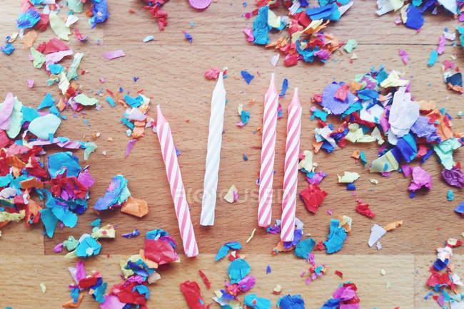 Vue de dessus des quatre bougies et coloré confetti — Photo de stock