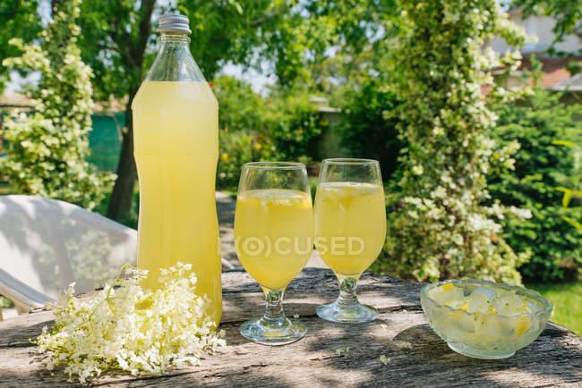 Elderflower lemonade in bottle and glasses on wooden table in garden — Stock Photo