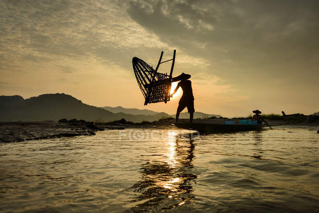 Silhouette of Man throwing fishing basket into Mekong river, Thailand — Stock Photo
