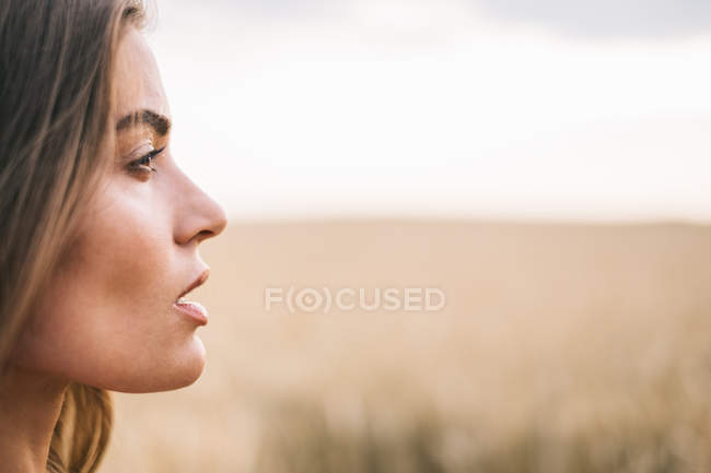 Portrait of beautiful woman standing in wheat field — Stock Photo