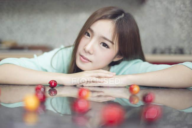 Junge Frau sitzt in Küche mit Kirschen auf Tischplatte — Stockfoto