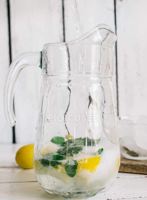 Brocca di vetro con limonata fresca lime, menta e cubetti di ghiaccio sul tavolo di legno — Foto stock