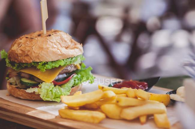 Hamburguesa y papas fritas sobre tabla de cortar contra fondo borroso - foto de stock