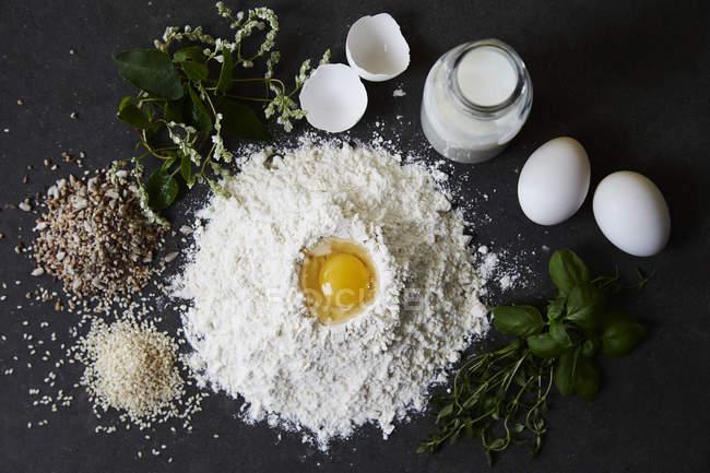 Мука, яйца, молоко, травы, рис и смешанных семена над деревянным столом — стоковое фото