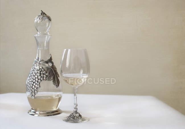 Графин и стакан белого вина белые служил таблицы — стоковое фото