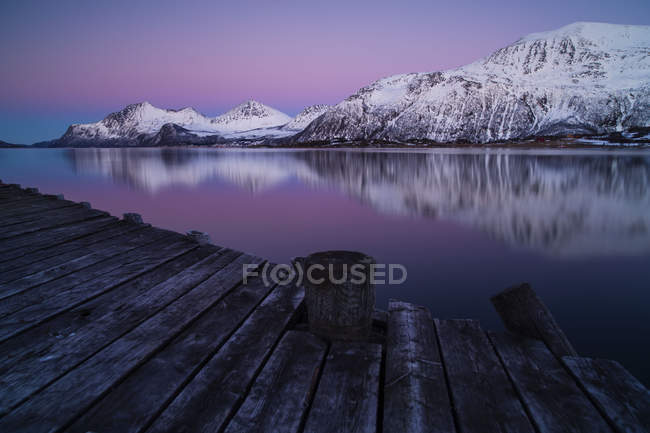 Snow covered mountains seen from a wooden jetty — Stock Photo