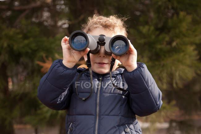 Мальчик смотрит через бинокль на улице — стоковое фото