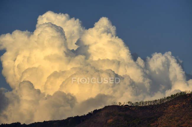 Живописный вид на холм и кучевые облака — стоковое фото