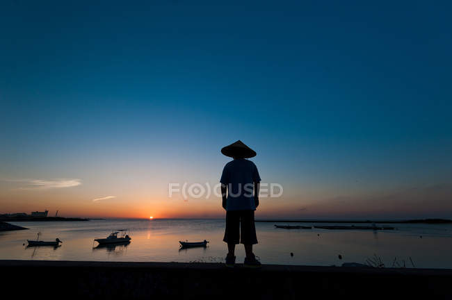 Silhouette of an unrecognizable person wearing a traditional hat,  Okinawa, Japan — Stockfoto