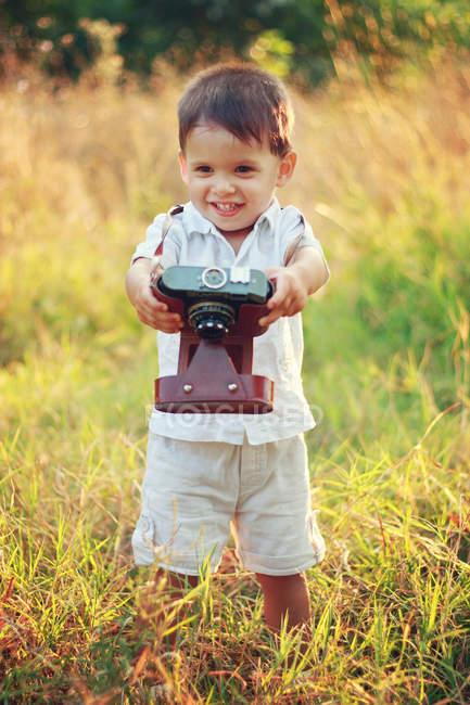 Улыбающийся мальчик держит винтажную камеру на траве — стоковое фото