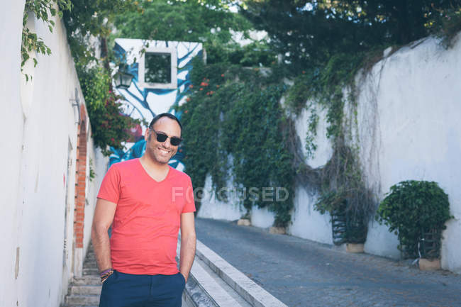 Smiling man standing on street with hands in pockets, Lisbon, Portugal — Stock Photo