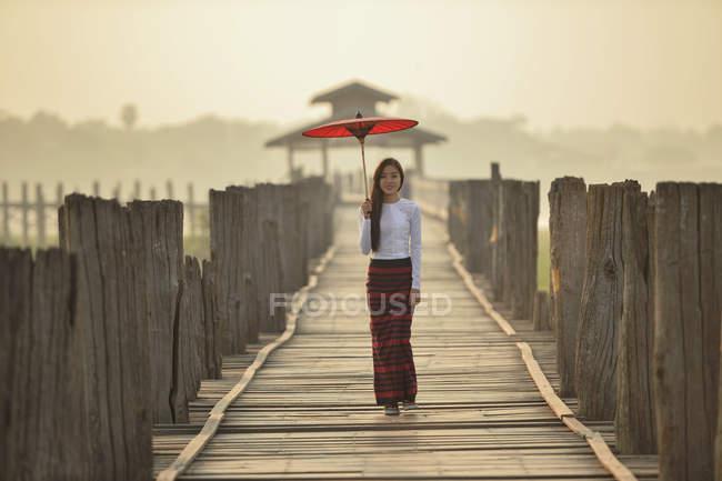 Frau spaziert mit traditionellem Regenschirm auf U-Bein-Brücke, Amarapura, Myanmar — Stockfoto