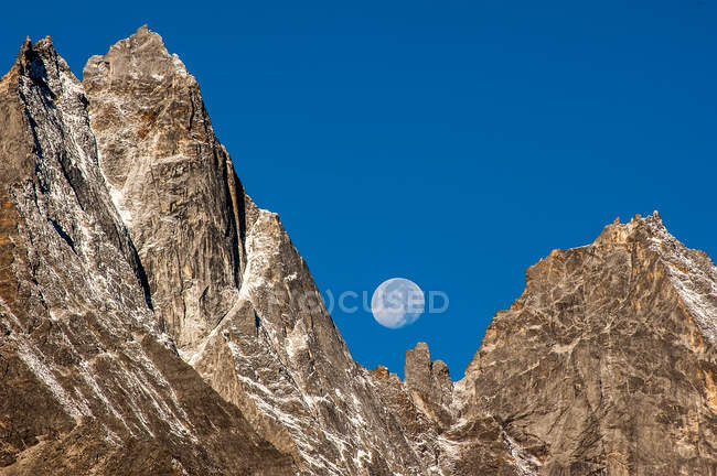 Himalayas, Kumbu, scenic view of moon visible behind rocky mountains in blue sky during day — Stock Photo