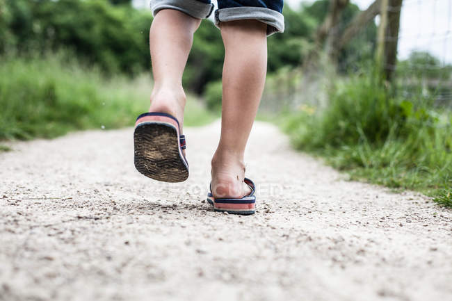 Rear view of little boy legs walking in flip flops — Stock Photo