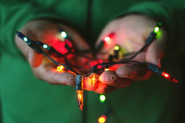 Acercamiento de manos humanas sosteniendo guirnalda brillante - foto de stock