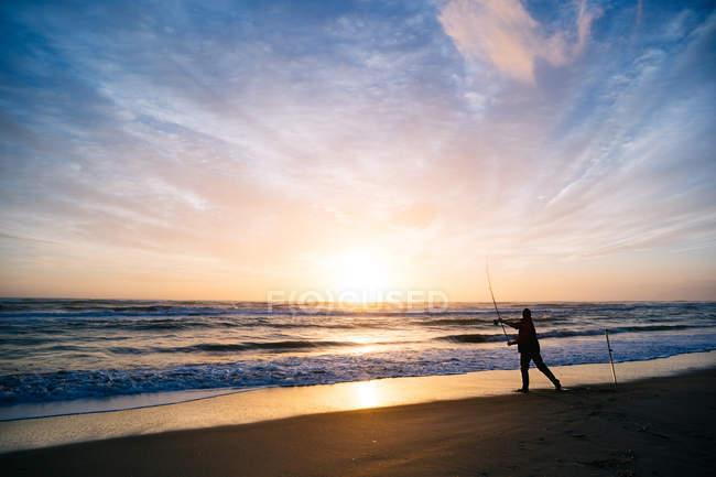 Silhueta de um pescador na praia ao pôr do sol, Pescia Romana, Lazio, Itália — Fotografia de Stock
