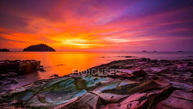 Мальовничий вид на захід сонця і драматичні небо над кам'янистий пляж — стокове фото