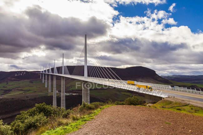 Живописный вид грузовиков, пересекающих мост Виадук Мийо, Миди Пиренеи, Франция — стоковое фото