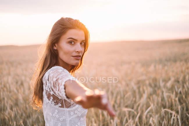 Женщина, стоящая на пшеничном поле с протянутой рукой к зрителю — стоковое фото