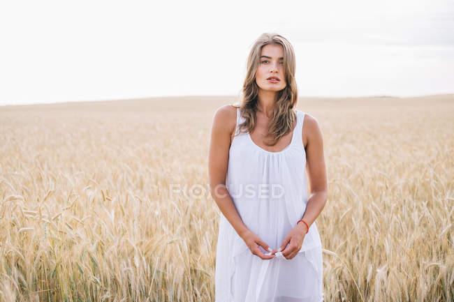 Портрет чувственной красивой женщины в белом платье, стоящей на пшеничном поле и смотрящей на зрителя — стоковое фото