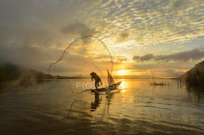 Силует людини кидаючи риболовля кошик у річки Меконг, Таїланд — стокове фото