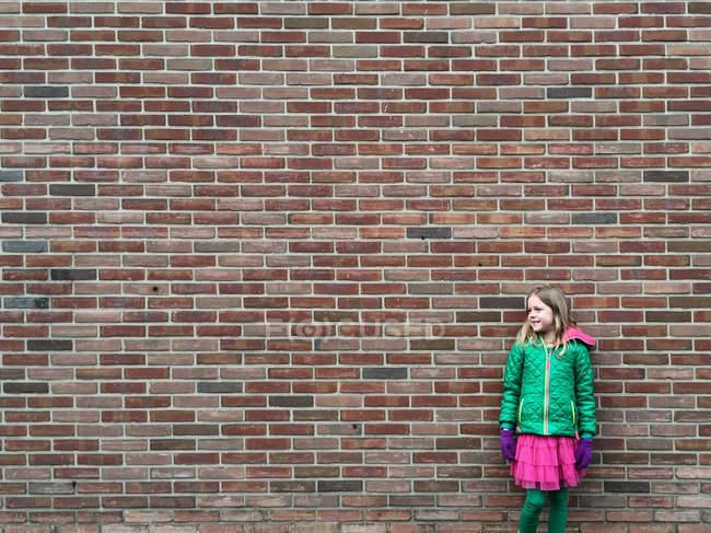 Chica sonriente de pie frente a la pared de ladrillo - foto de stock