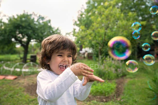 Chico riendo jugando con burbujas de jabón - foto de stock
