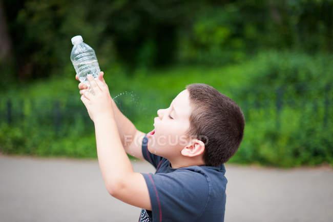 Eau potable garçon de trou au fond de la bouteille d'eau — Photo de stock