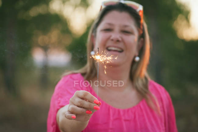 Portrait of a happy middle aged woman holding sparkler and laughing — Stock Photo
