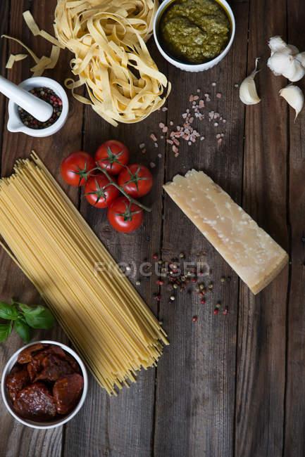 Pasta, pesto, ajo, tomates y parmesano en la mesa - foto de stock
