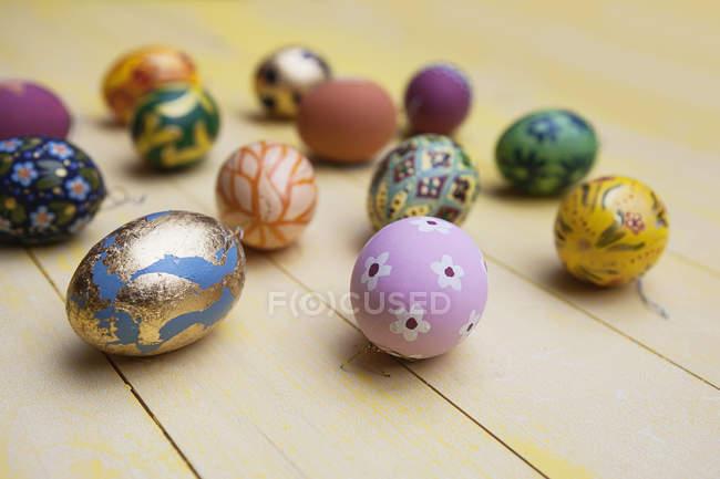 Close-up de mão pintada de ovos de Páscoa na mesa de madeira — Fotografia de Stock