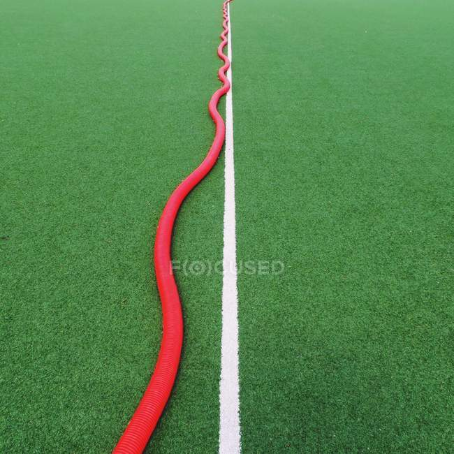 Single white line on green sports field, and red pipe — Stock Photo