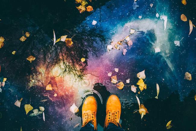 Zugeschnittenes Bild der männliche Füße und Reflexion des Nachthimmels und Raum in Pfütze Wasser — Stockfoto