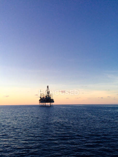 Scenic view of oil rig at sunset — Stock Photo