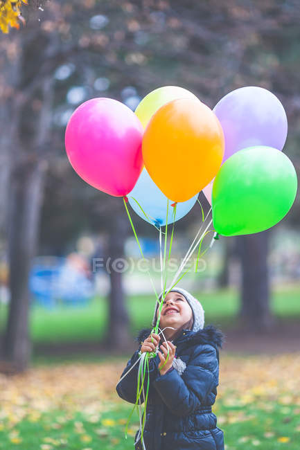Portrait of a smiling girl holding colorful balloons outdoors — Stock Photo