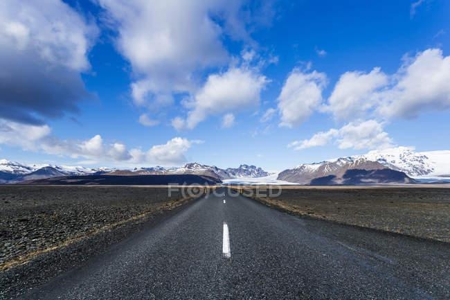 Мальовничим видом порожній-роуд, гірський хребет у фоновому режимі, Ісландія — стокове фото