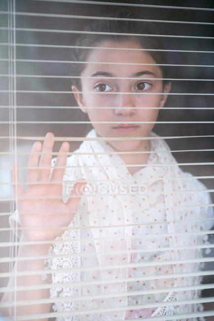 Девочка смотрит через Персидский жалюзи на окна — стоковое фото