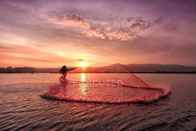 Силует рибалки ловлять рибу при сходом сонця, Rawapening озеро, Java, Індонезії — стокове фото