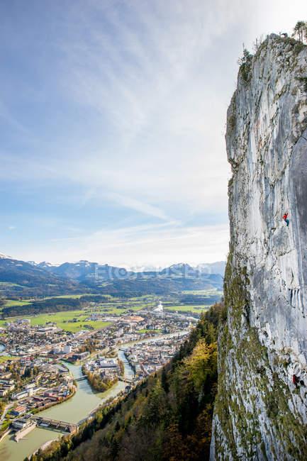 Homem escaladas alto acima da cidade, Hallein, Salzburg, Áustria — Fotografia de Stock