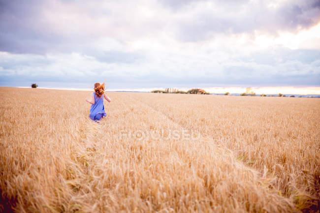 Ginger girl running through barley field — Stock Photo