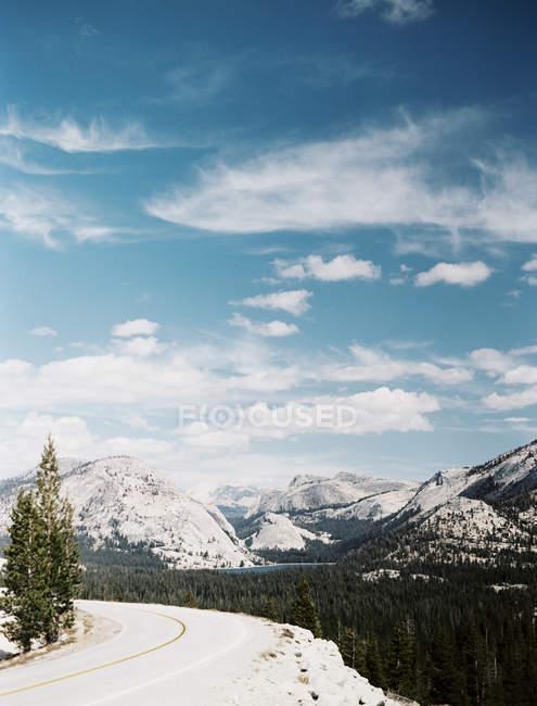 Ciel bleu avec des nuages, de montagnes enneigées et de forêt derrière la route. Route à travers le Parc National de Yosemite, Amérique, Usa — Photo de stock