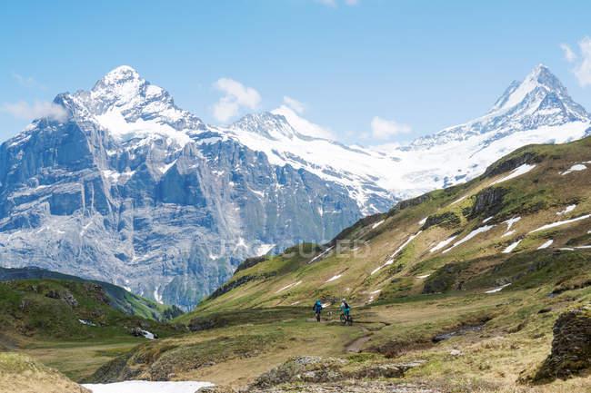 Two women mountain biking in swiss alps, Grindelwald, Switzerland — Stock Photo