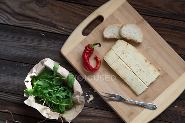 Повышенные вид сыра, Чили, рукколой и хлеб за деревянным столом — стоковое фото
