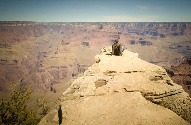 Junger Mann sitzt auf der Kante des Grand Canyon, Arizona, Usa — Stockfoto