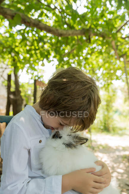 Boy holding fluffy pet rabbit — Stock Photo