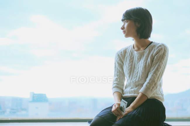 Портрет молодой женщины, выглядывающей в окно — стоковое фото